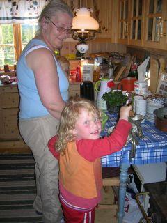 Leah Christine hjelper mormor med å dra kjøttkverna når  vi maler osten til gommen.