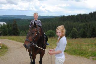 Malin med hesten Tom på ridetur med Adrian